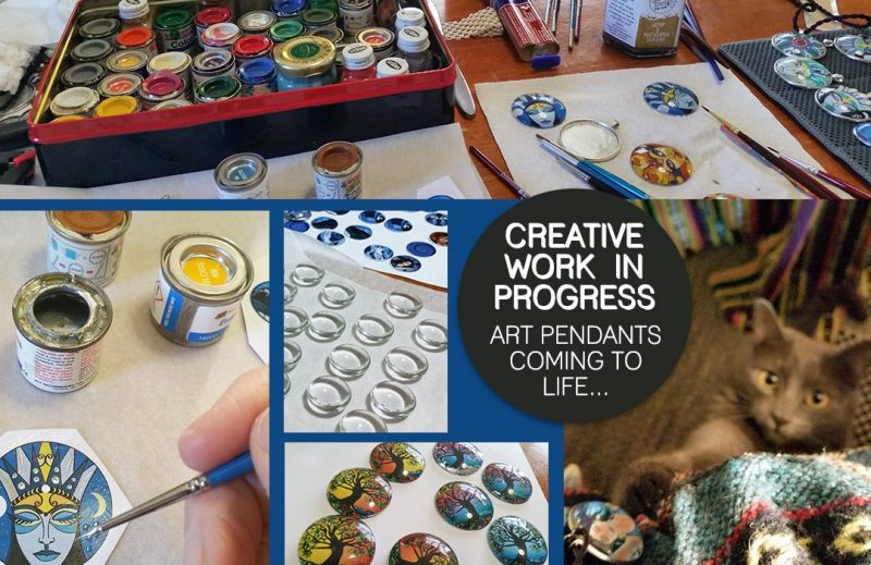 Art pendants in the making, enamel paint, glass dome cabochons, paint brushes, WIP and cat