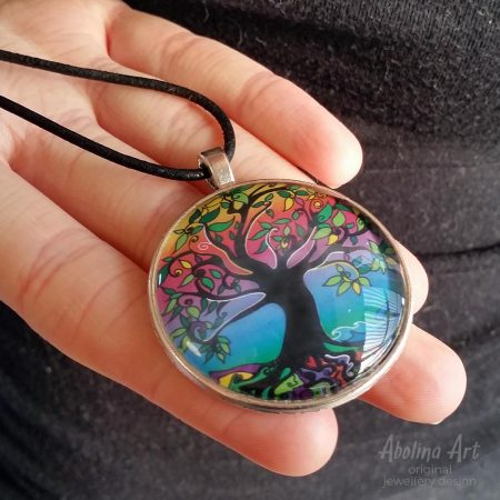 Tree of Life Psychedelic Dawn pendant held in model's hand