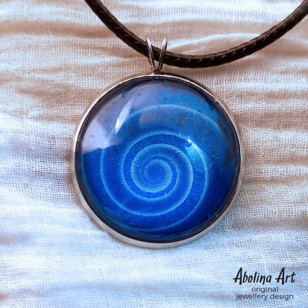 Nine Lives Blue Spiral pendant on white fabric background