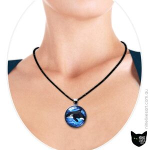 Orca swimming in blue waves 25mm art pendant strung on cord - worn by model