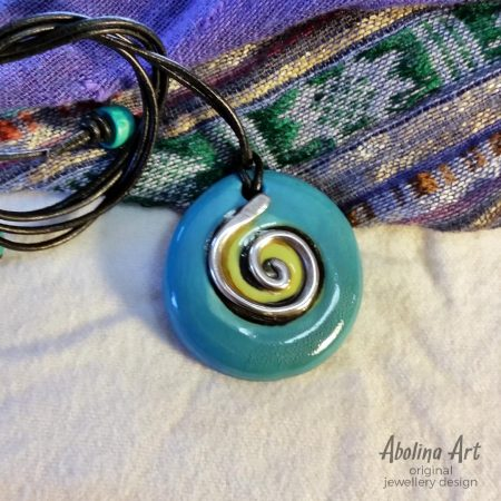 Turquoise stoneware pendant with silver spiral strung on leather cord