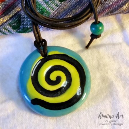 Turquoise spiral pendant strung on leather cord