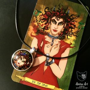 Devilish art pendant displayed with tarot card