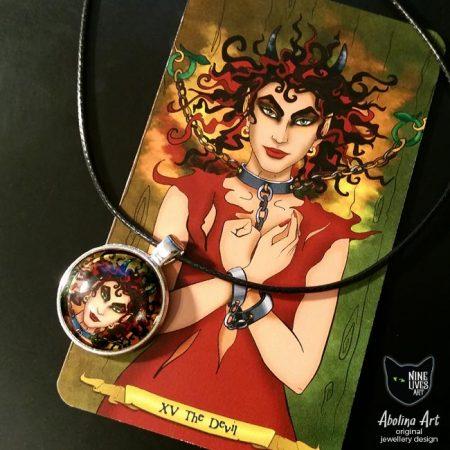 Devilish art pendant displayed with tarot card