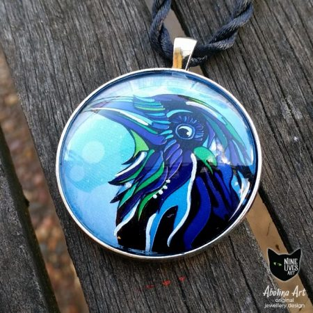 Striking raven painted in blue and green hues set in 40mm antique silver metal with glass cabochon