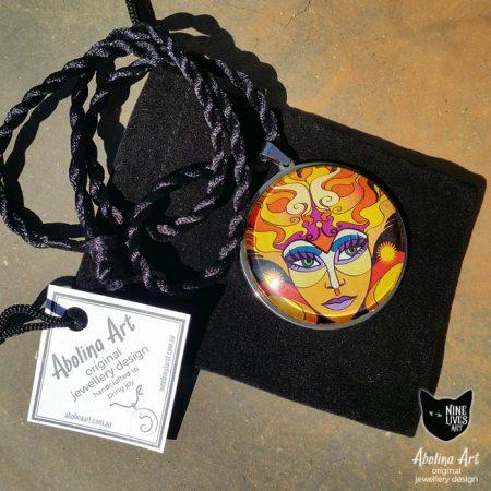 Sun Goddess art pendant displayed with gift tag and black velvet bag