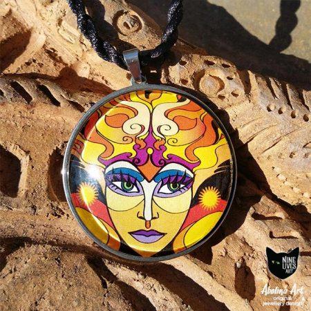 Sun Goddess 40mm art pendant photographed in full sun on terracotta background