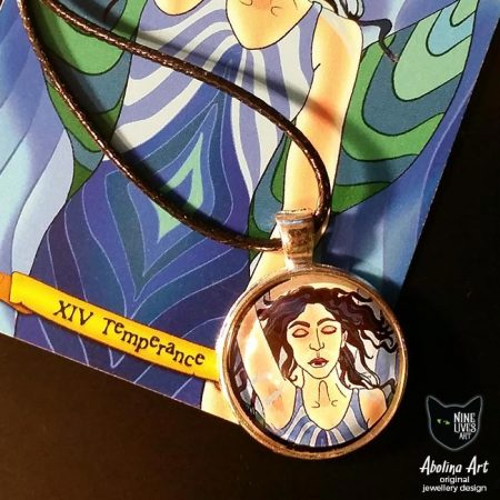 25mm art pendant featuring Temperance from Nine Lives Tarot, photographed with card artwork (detail) in background