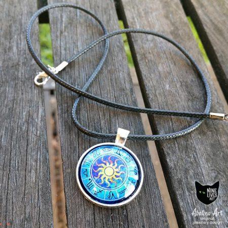 Blue art pendant featuring zodiac wheel strung on black cord