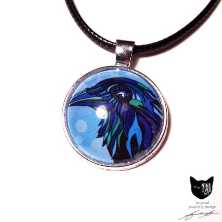 Blue raven artwork sealed under glass cabochon with antique silver metal pendant setting and black cord
