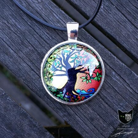 Art pendant featuring tree of life clad in summer colours, sealed under glass cabochon and strung on black cord