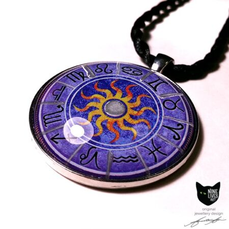 close up view of purple zodiac pendant with star signs and sun in the centre