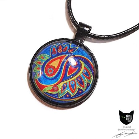 Art pendant with paisley inspired artwork in bold colours on blue in black bezel, with glass cabochon sealing the artwork