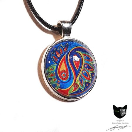 Art pendant with paisley inspired artwork in bold colours on blue with glass cabochon sealing the artwork