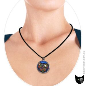 Bold colourful cat on blue background sealed under glass cabochon and strung on cord