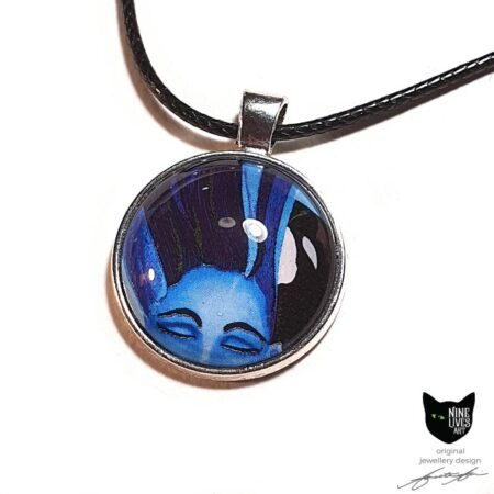 Art pendant featuring woman's face and orca under water in blue hues, artwork sealed under glass dome and set in silver coloured bezel