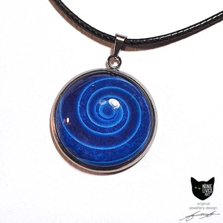 Art pendant featuring deep blue swirl from Nine Lives tarot card back, sealed under glass cabochon with bezel setting