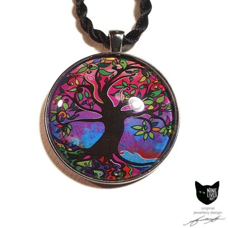 Gorgeous tree of life art pendant featuring bright pink and purple hues accentuated by splashes of blue - artwork sealed under glass cabochon and strung on cord for wearing