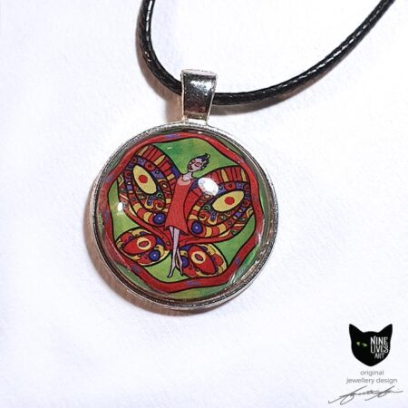 Striking art pendant featuring fairy with butterfly wings in bright orange red tones on green background, cabochon setting with silver coloured bezel strung on black cord
