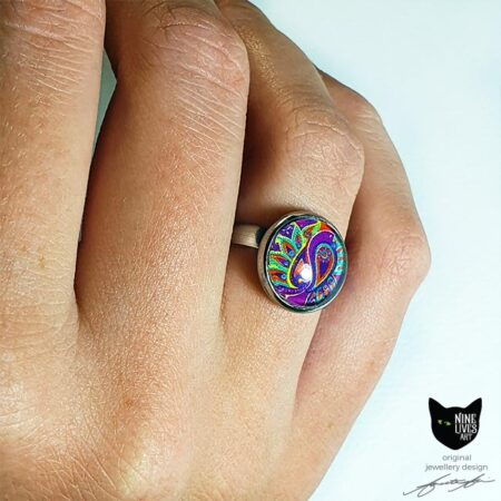 Model wearing 12mm pink, purple and orange paisley ring set under glass cabochon
