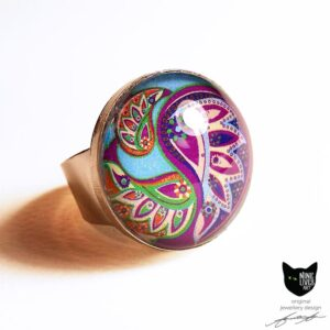 Large 25mm ring featuring paisley inspired artwork on turquoise background with bright colours
