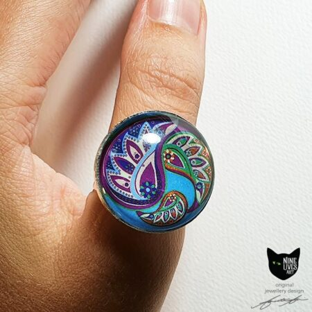 Model wearing 25mm green, purple and turquoise paisley ring set under glass cabochon