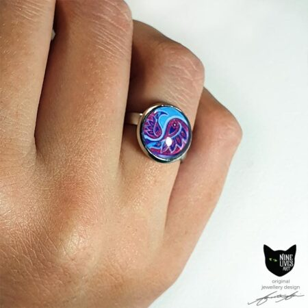 Model wearing 12mm turquoise and pink paisley ring set under glass cabochon