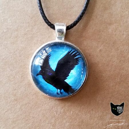 Black raven flying on a turquoise blue sky background - 25mm silver coloured pendant setting