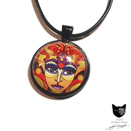 Art pendant featuring sun goddess in vibrant warm colours, sealed under glass dome with black bezel and pendant cord