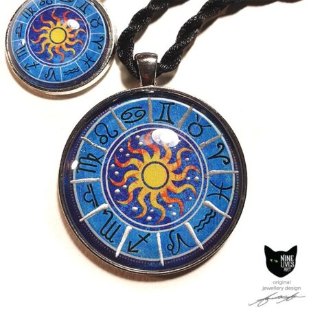 Two art pendants featuring the 12 zodiac star signs and sun in the centre on blue background, sealed under cabochon
