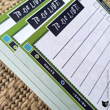 Closeup view of three to do list notepads with colourful border design