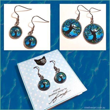 Tree of Life earrings displayed on blue background