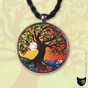 Tree of Life pendant displayed on top of enlarged tree artwork